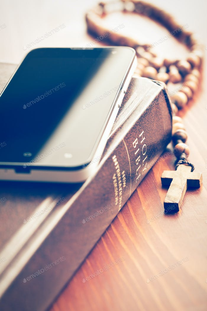 smartphone with holy bible and rosary