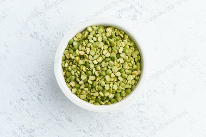 Grüne Erbsen in weißer Schüssel auf weißem Hintergrund. Getrocknete Getreide in Tasse, vegane Lebensmittel. Draufsicht, Nahaufnahme.