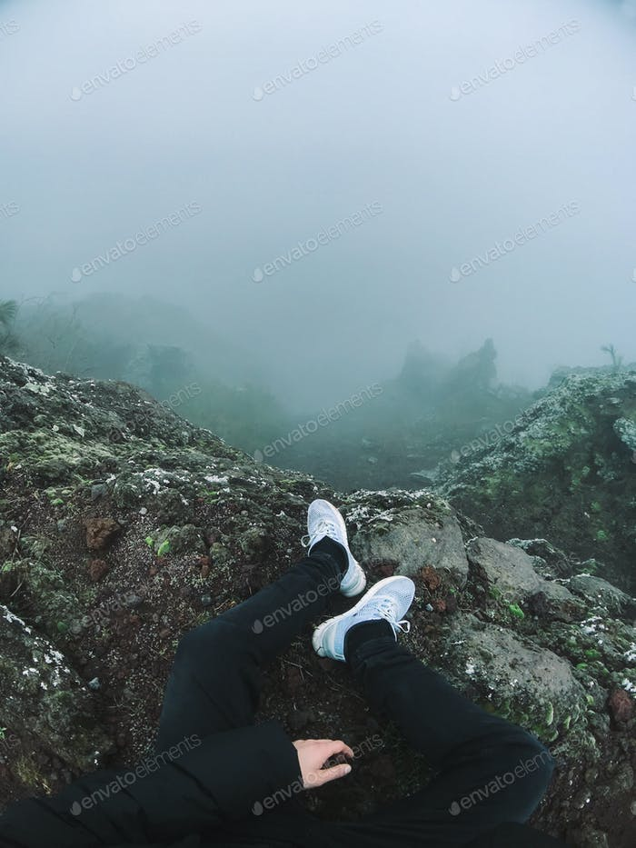 Man on cliff look at the fog