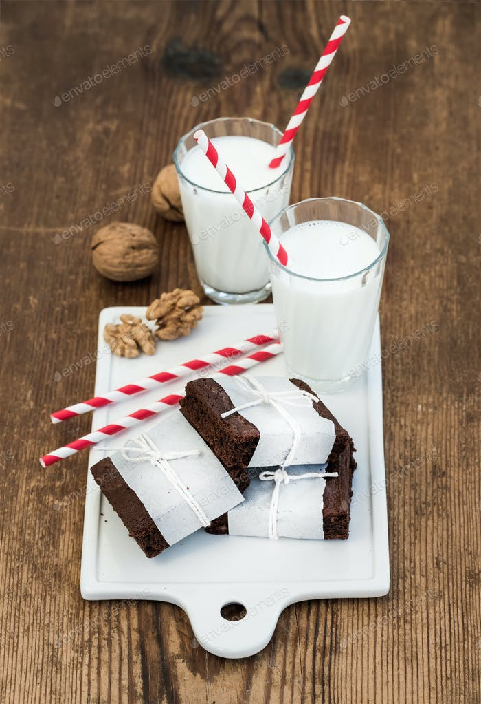 Chocolate brownie slices wrapped in paper and tired with rope, glasses of milk