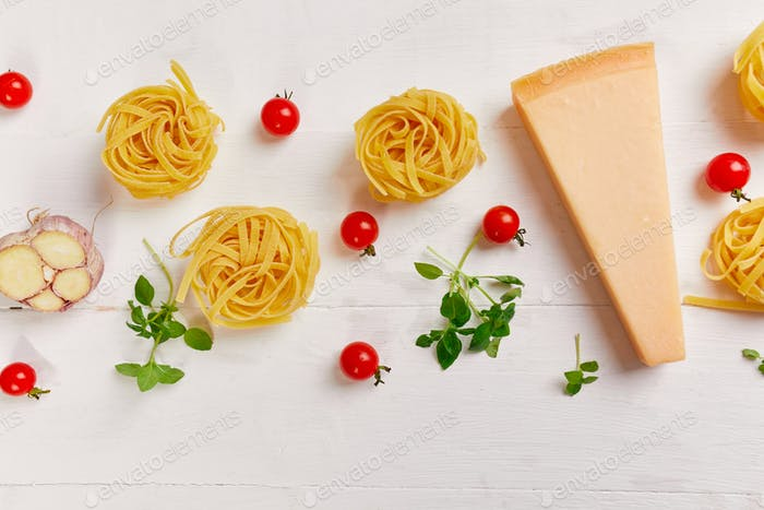 Ingredients for cooking pasta  - tagliatelle, tomato, garlic, basil, parmesan cheese