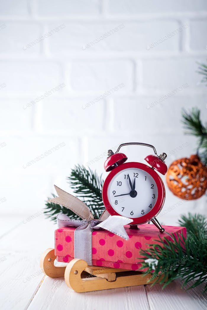 Xmas greeting card. Christmas background with snow fir tree and alarm clock. View from above