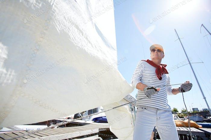 Sailor releasing sail in sunlight