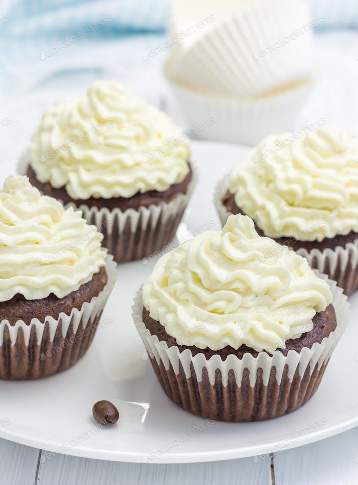 Schokoladen-Cupcakes mit Ricotta-Käse Zuckerguss auf dem weißen Teller