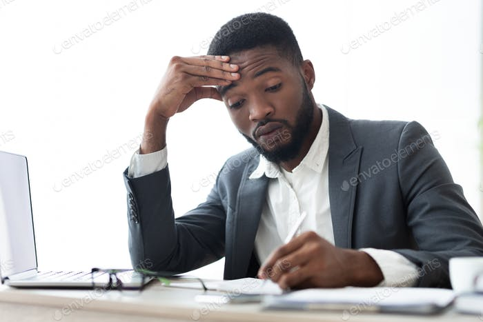 Busy african american businessman signing contracts or agreements at workplace