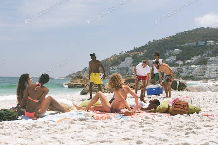 Diverse group of friends relaxing and enjoying at beach on a sunny day while men holding cooler