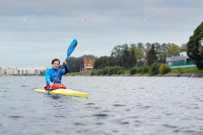 Professionelle kaukasische männliche Athlet paddeln entlang des Flusses in gelbem Kajak