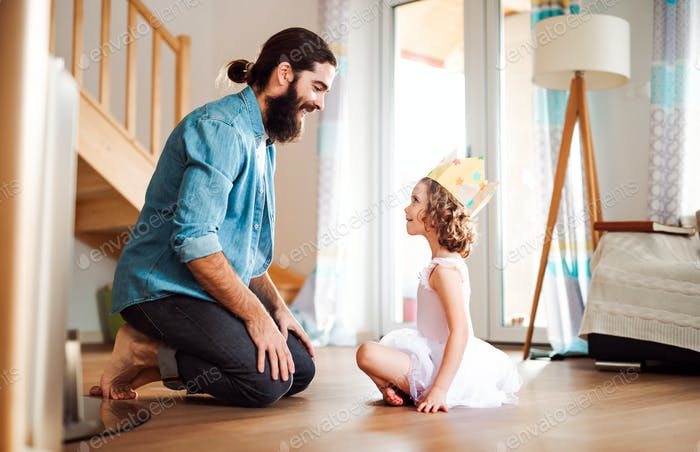 Side view of small girl with a princess crown and young father at home, playing.