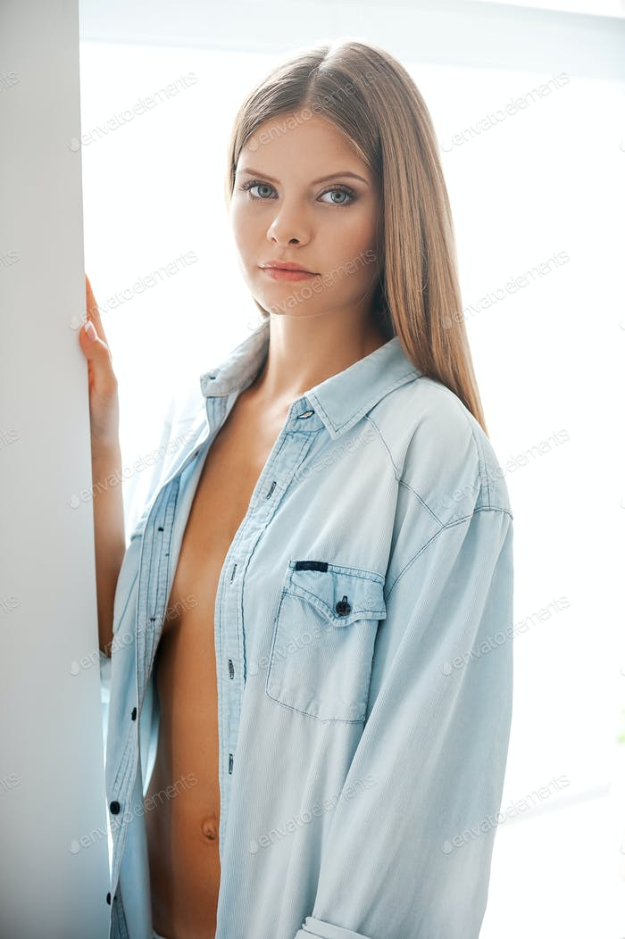 Pure feminine beauty. Confident young woman in shirt looking at camera while standing against window
