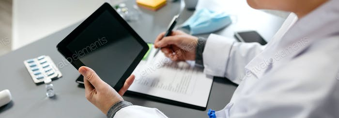 Unrecognizable female doctor using tablet while working