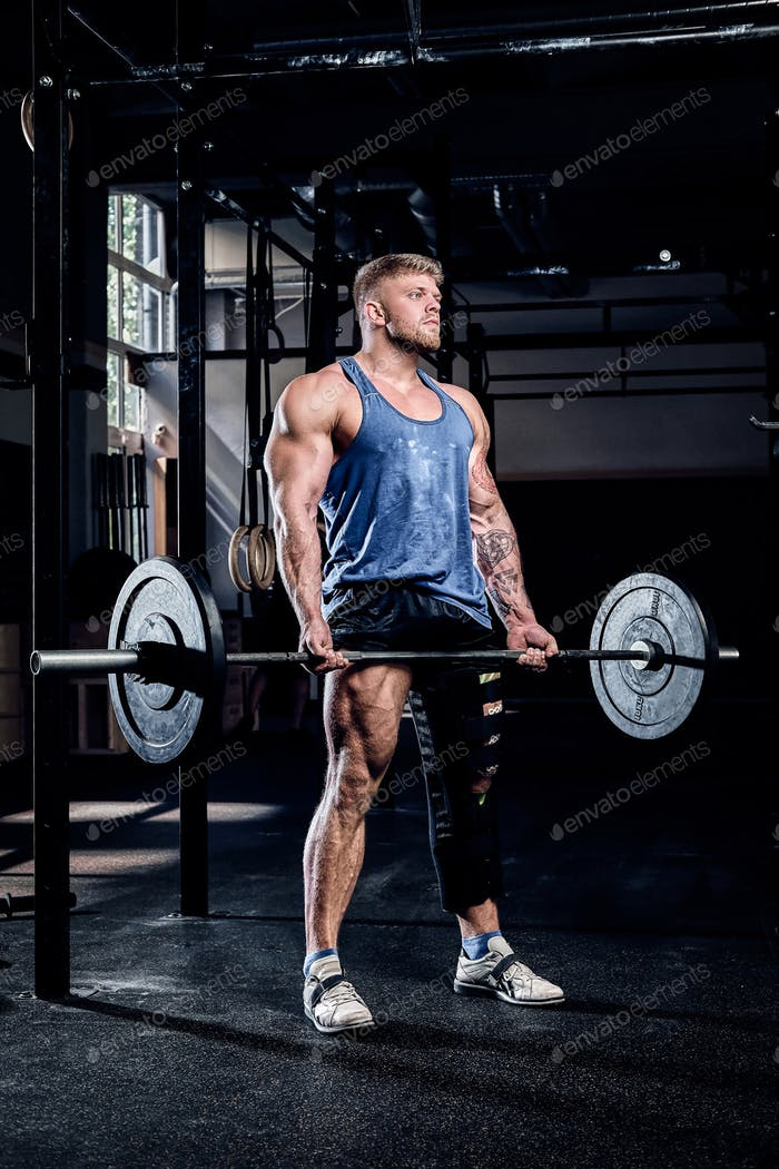 Powerlifter with a bandage on a leg, doing exercises with a barbell, injury recovery.