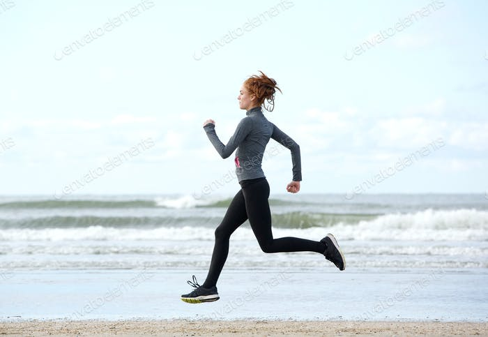 Healthy young woman running at the beach