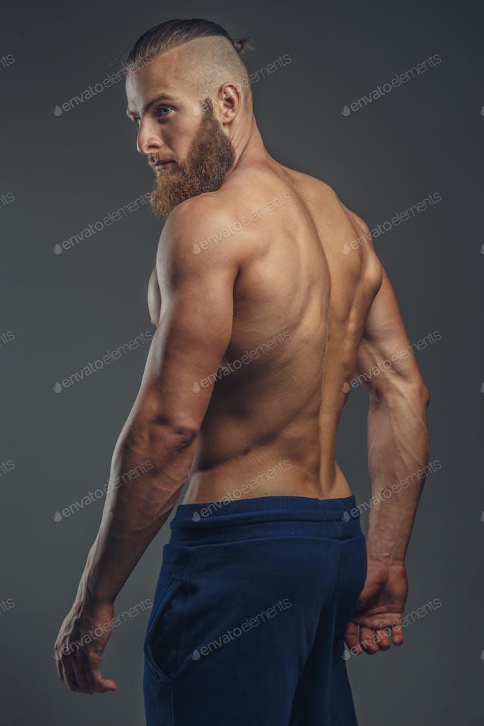 Shirtless muscular bodybuilder with beard