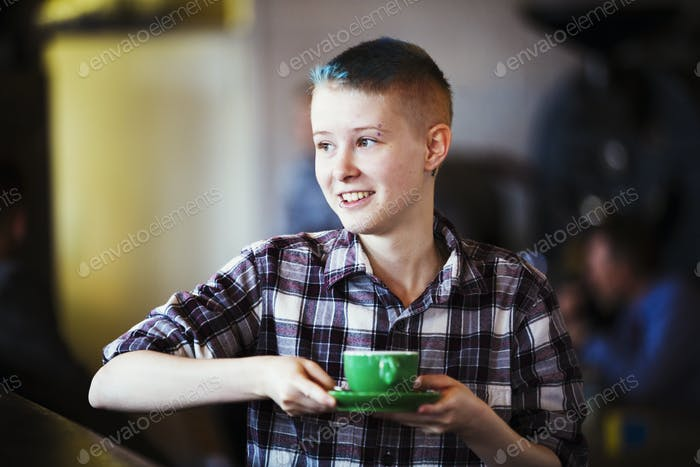 Specialist coffee shop. A young persion carrying a cup of coffee.
