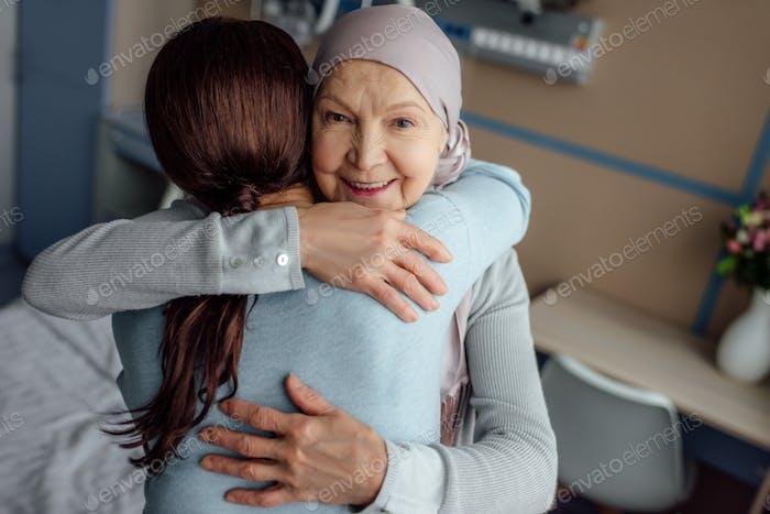 happy senior woman in kerchief embracing daughter in hospital