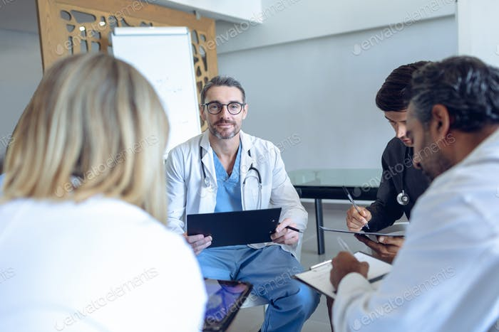 Caucasian male doctor looking at camera while sitting in circle with team in meeting