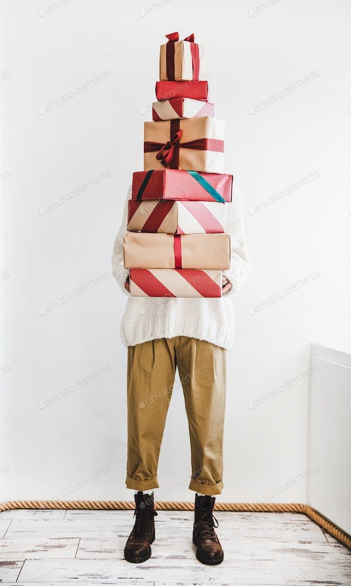 Human figure holding pile of Christmas festive gift boxes