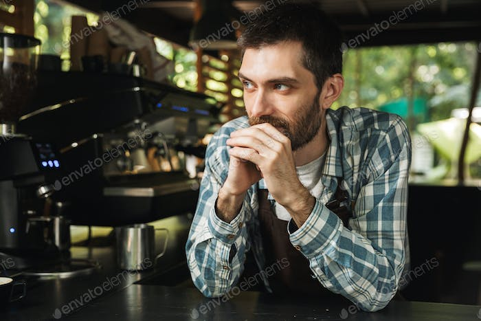 Portrait of attractive barista guy smiling while working in stre