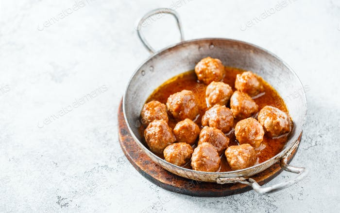 Hot meatballs in tomato sauce in a old frying pan