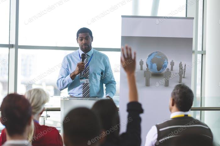 Businesswoman raising hand during business seminar in modern office building
