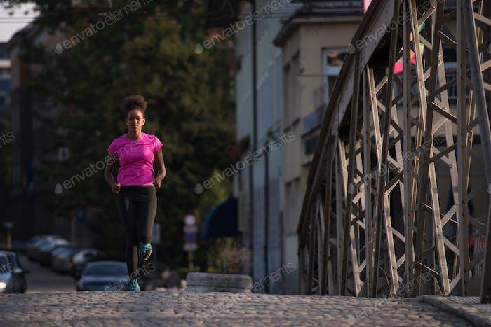 African American Frau läuft über die Brücke