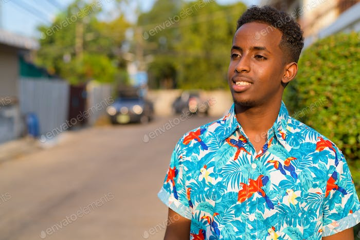 Face of happy young African tourist man with Afro hair thinking outdoors