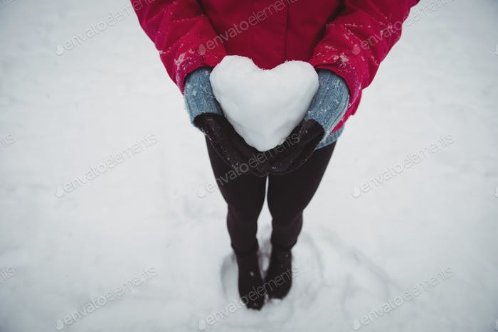 Woman in warm clothing holding snowy heart