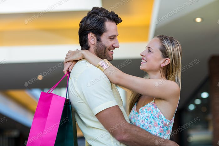 Smiling couple embracing and looking at each other at shopping mall