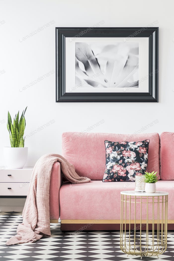 Floral pillows and blanket on pink couch in living room interior