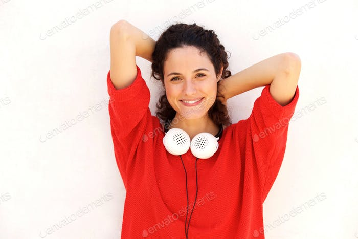Close up attractive  young woman with headphones and hands behin