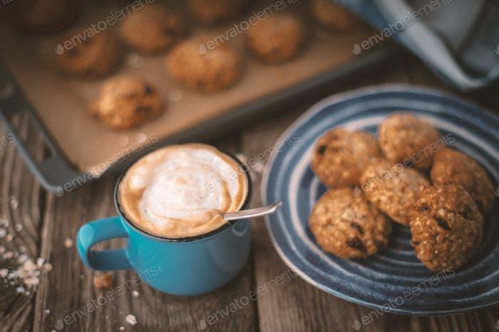 Backblech und eine Platte mit Haferflocken Cookies auf dem Holztisch