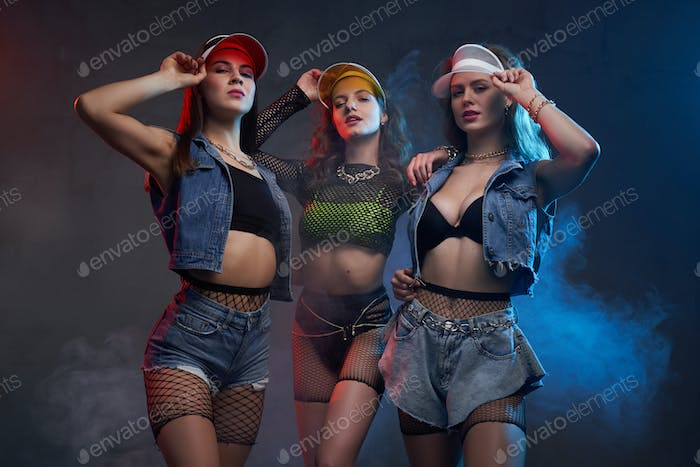 Confident and sexy girls in stylish clothing posing in studio