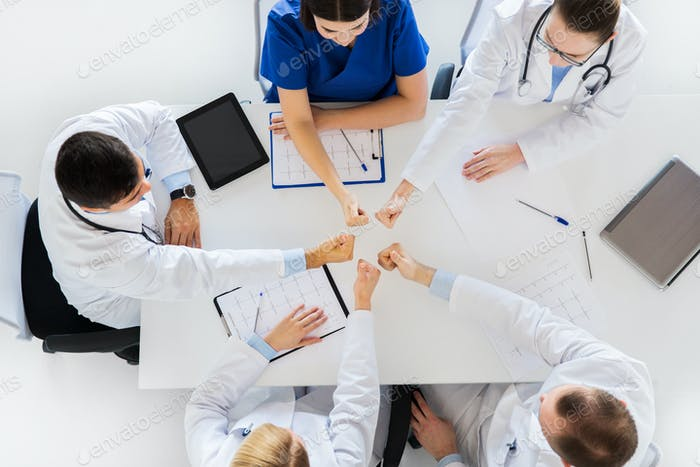 group of doctors showing thumbs up over table