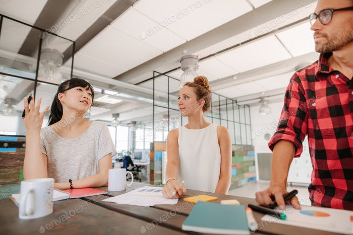 Group of multiracial coworkers meeting in creative office