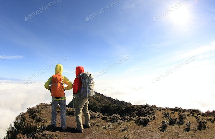 Two women hiking friends on mountain peak
