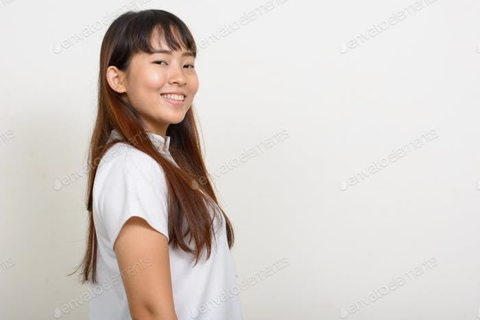 Profile view of happy young Asian woman looking at camera