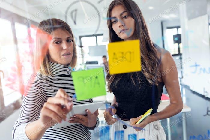 Zwei Business-junge Frauen arbeiten zusammen an Wand Glas mit Post it Aufkleber