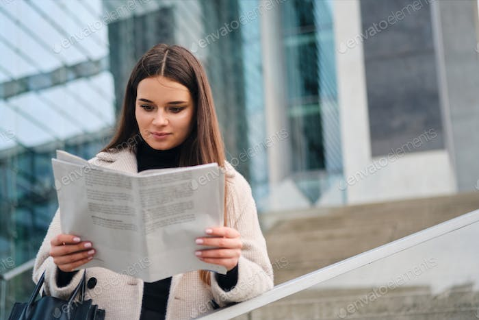 Beautiful stylish businesswoman thoughtfully reading newspaper in center