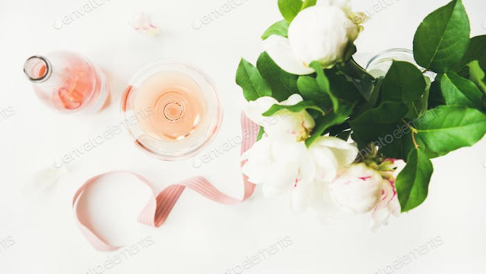 Rose wine, decorative ribbon and peony flowers over white background