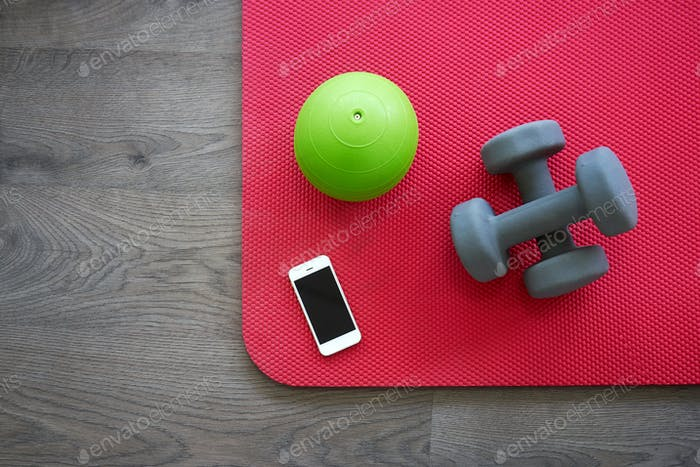 Gym equipment on red mat as background, top view