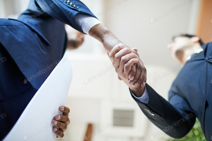 Businessmen shaking hands after signing contract