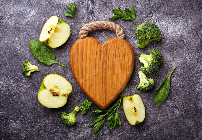 Green food background with wooden board in shape of heart