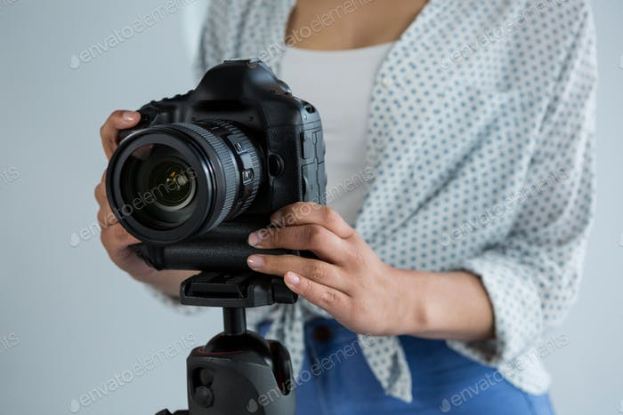 Mid section of female photographer adjusting digital camera