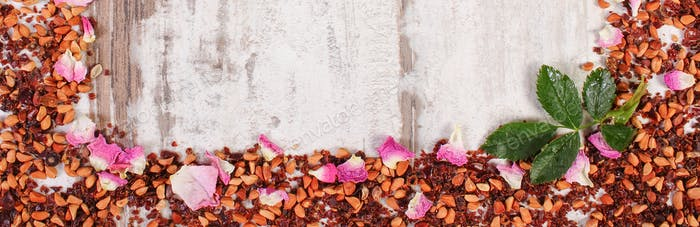 Frame of dried wild rose petals and tea grains on old board, copy space for text