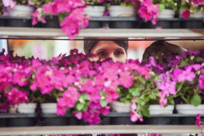 Woman taking a flower from the shelves