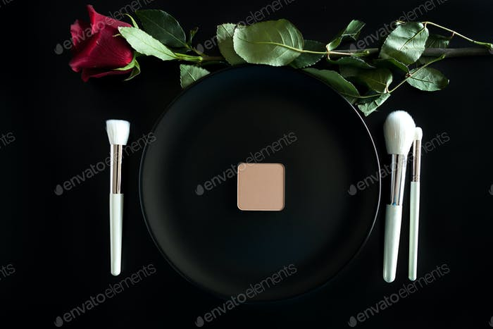 Conceptual image of make up brushes next to dinner plate