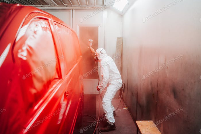 automotive industry manufacturing - mechanic engineer using spray gun and painting a red car