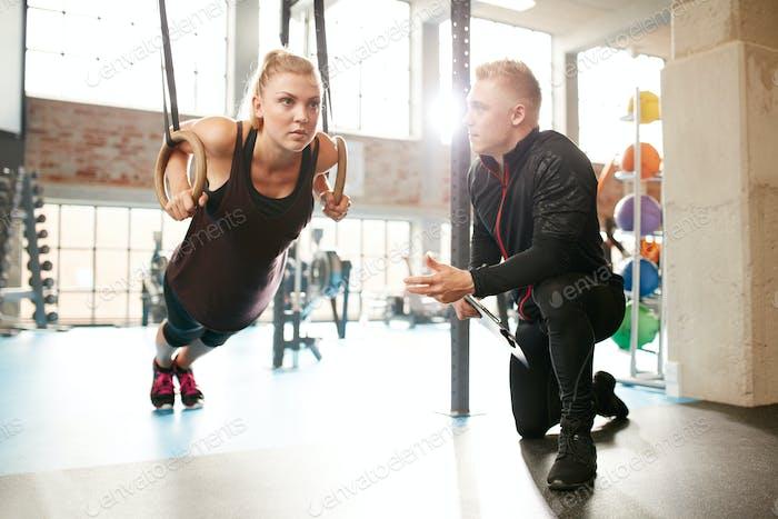Frau, die mit einem Trainer in der Turnhalle trainieren