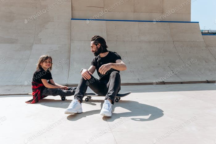 Young father and his son dressed in the casual clothes are siting on the skateboards in a skate park