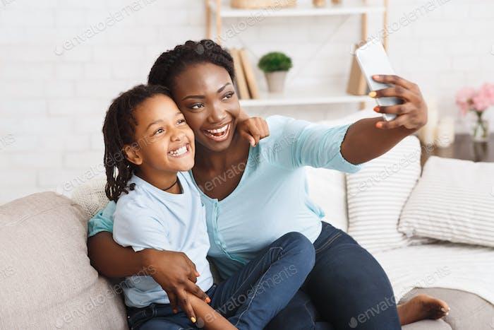 Glückliche schwarze Mutter und Tochter nehmen Selfie